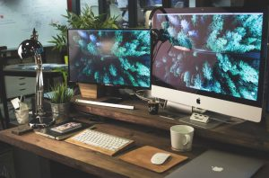 Wooden desk setting with two large computer screens, white Mac keyboard, mouse, white mug, black lamp, green plant, black notebook